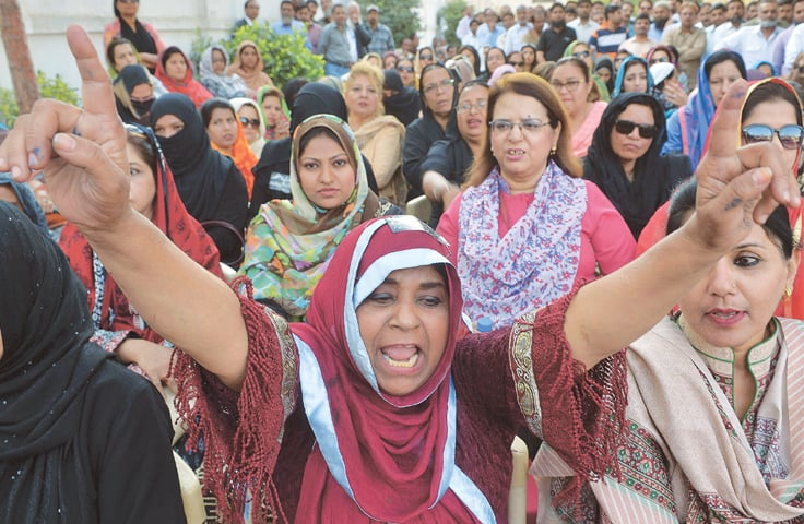 KARACHI: A woman employee of the Pakistan International Airlines raises a slogan as she leads her colleagues during a protest here on Wednesday.—AFP