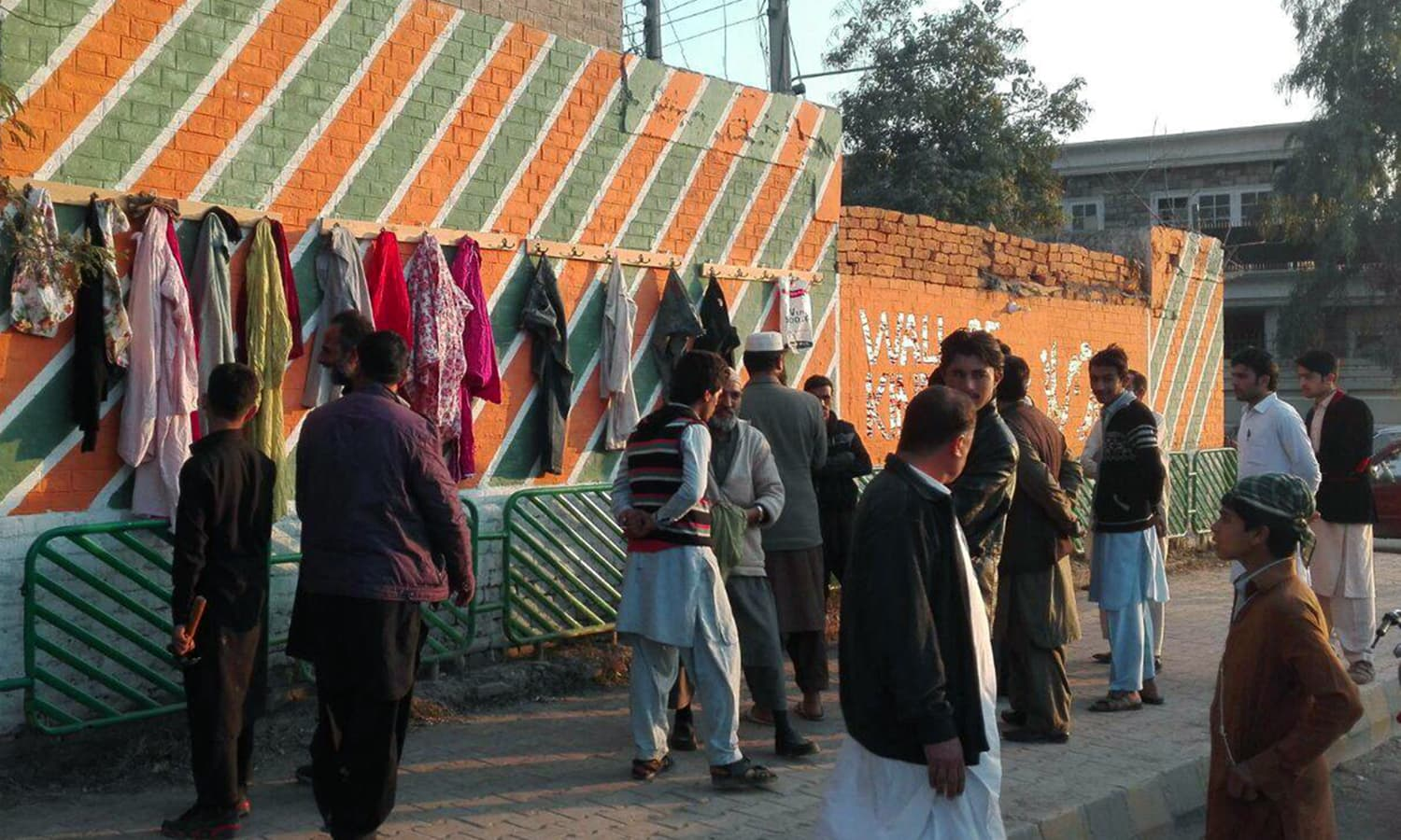 Peshawarites contribute clothes to the Wall of Kindness. — Photo by Asad Lodhi