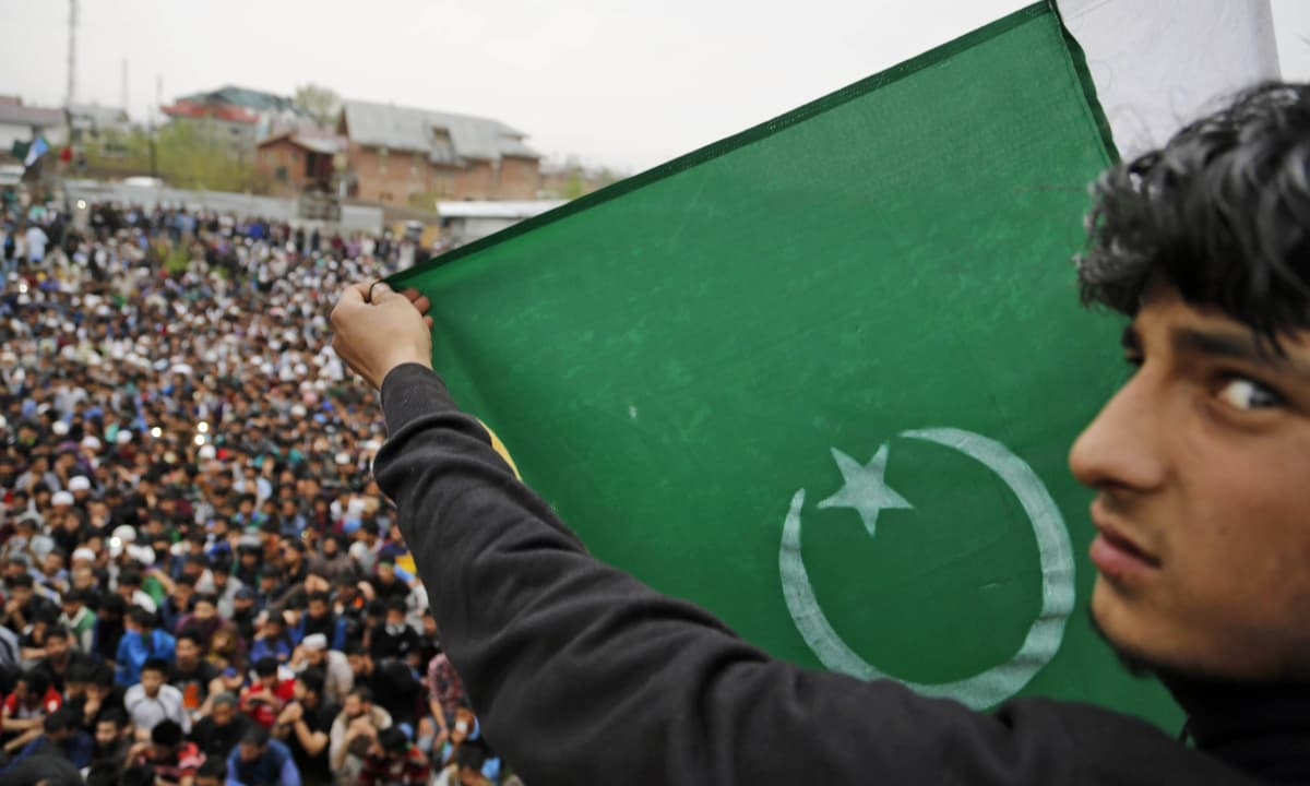 A supporter of senior separatist leader, Syed Ali Shah Geelani, carries a Pakistani national flag during a rally in Srinagar   Mukhtar Khan, AP