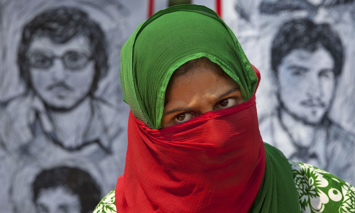 A Kashmiri woman sits in front of a banner showing portraits of missing Kashmiris   Dar Yasin, AP