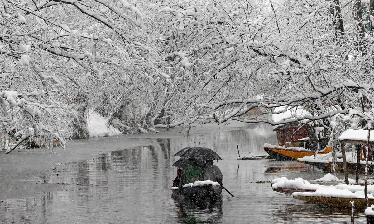A passenger boat moves on Dal Lake during December snowfall | Mukhtar Khan, AP