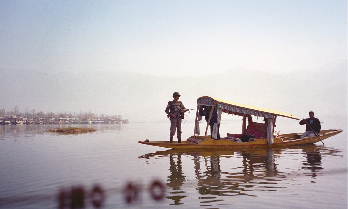 A soldier stands guard on a boat on Dal Lake | Dilnaz boga