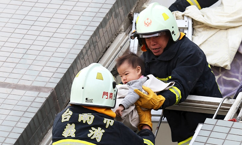 Rescue workers remove a baby from the site where a 16-storey apartment building collapsed after an earthquake hit Tainan, February 6, 2016.—Reuters