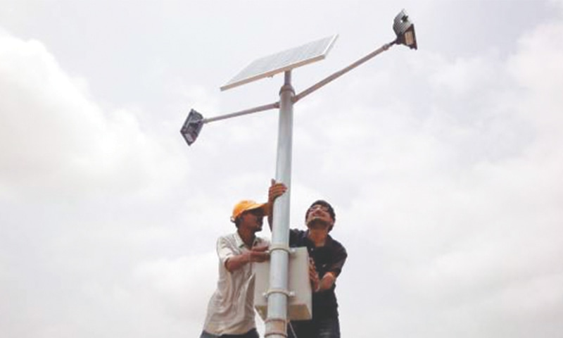 Mechanics mount a solar panel on a pole in Jati village in the coastal district of Thatta in Sindh.—Reuters file photo