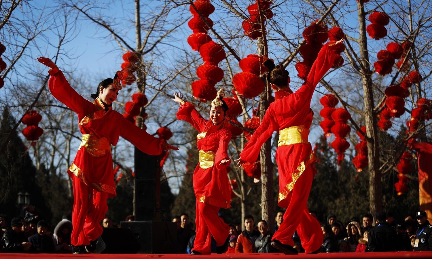 Chinese dancers dressed in traditional costumes perform a cultural dance on stage during a temple fair. ─ AP