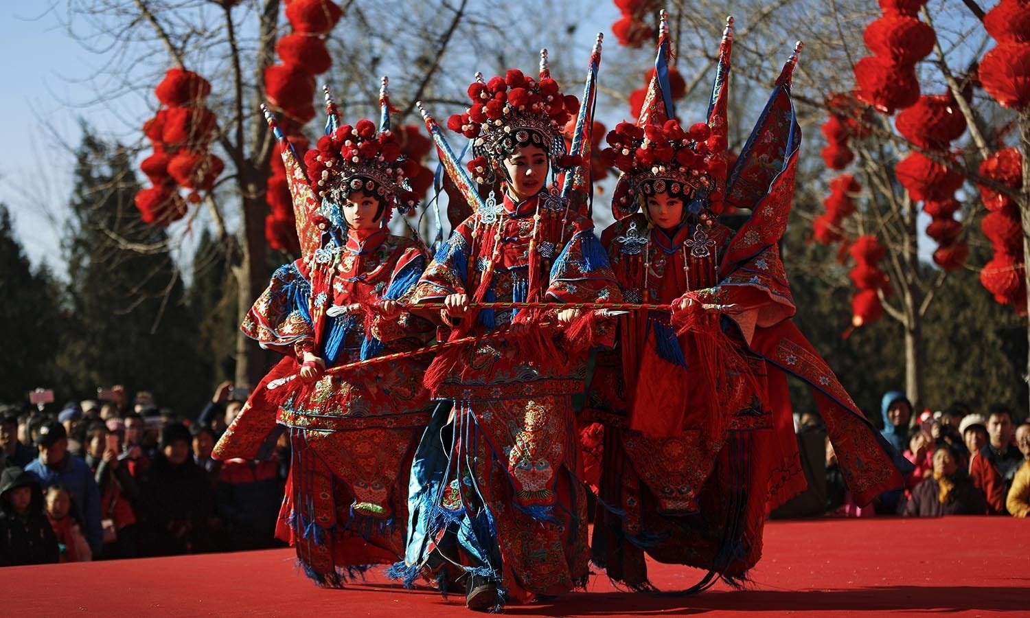 A Chinese dancer dressed in traditional costume performs a cultural dance on stage during a temple fair. ─ AP