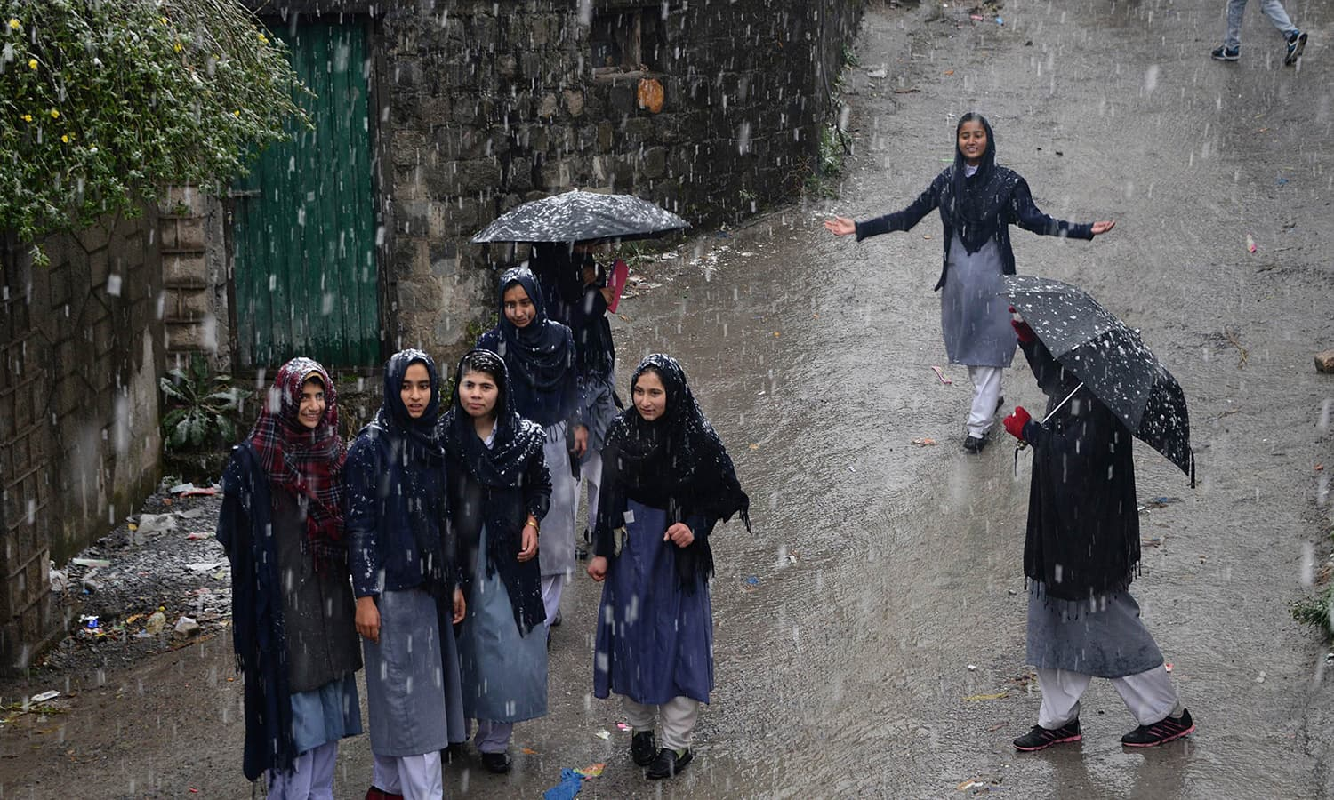 Female students come out from their school under snow fall in Muzaffarabad, the capital of Azad Kashmir. ─AFP