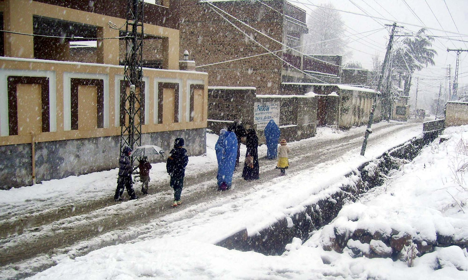Commuters passing through a snow covered road in Abbottabad. ─PPI