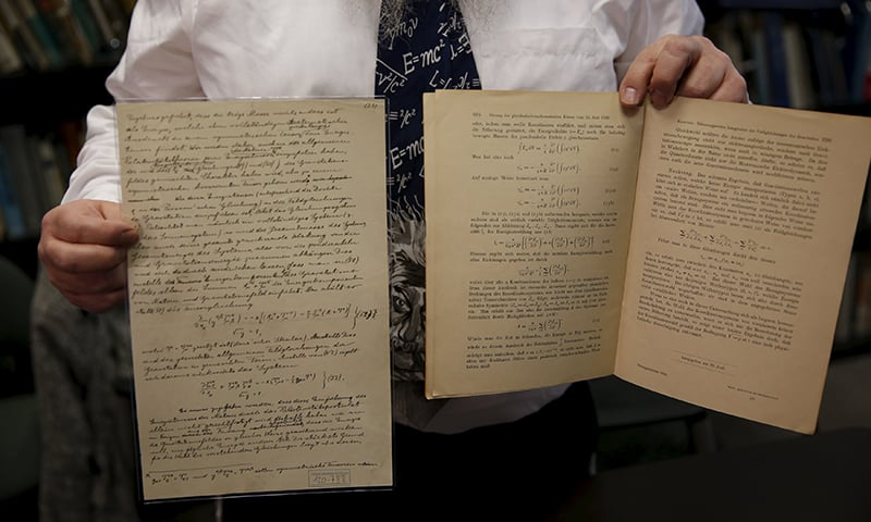 Roni Gross, curator of the Hebrew University's Albert Einstein Archive, displays original documents related to Albert Einstein's hypothesis of the existence of gravitational waves during a news conference in Jerusalem.─Reuters