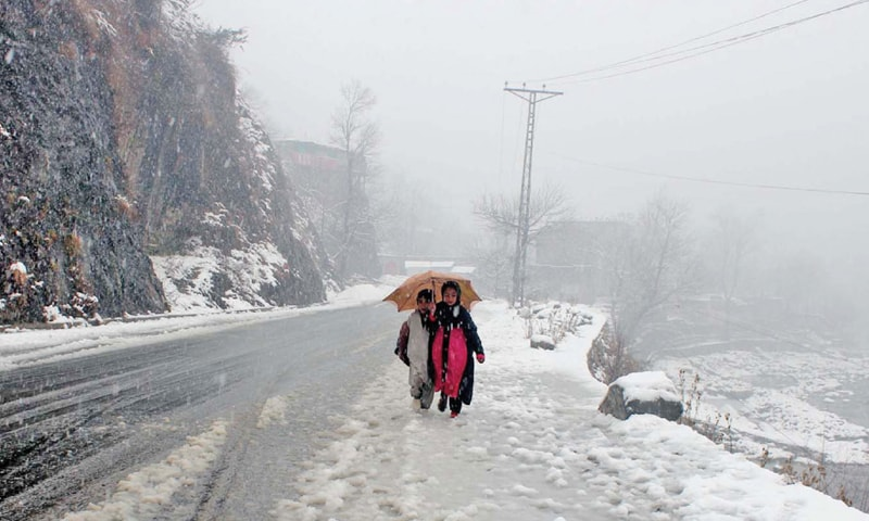 Minors walk on a road during snowfall in Shangla on Thursday. — Photo by Umar Bacha