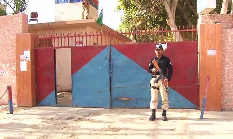 A police officer stands on guard near the Mobina Town police station. ─ DawnNews