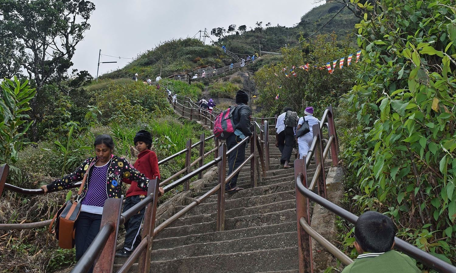 Some visitors walk up while others rest on steps to Adam's Peak. ─Photo by the author