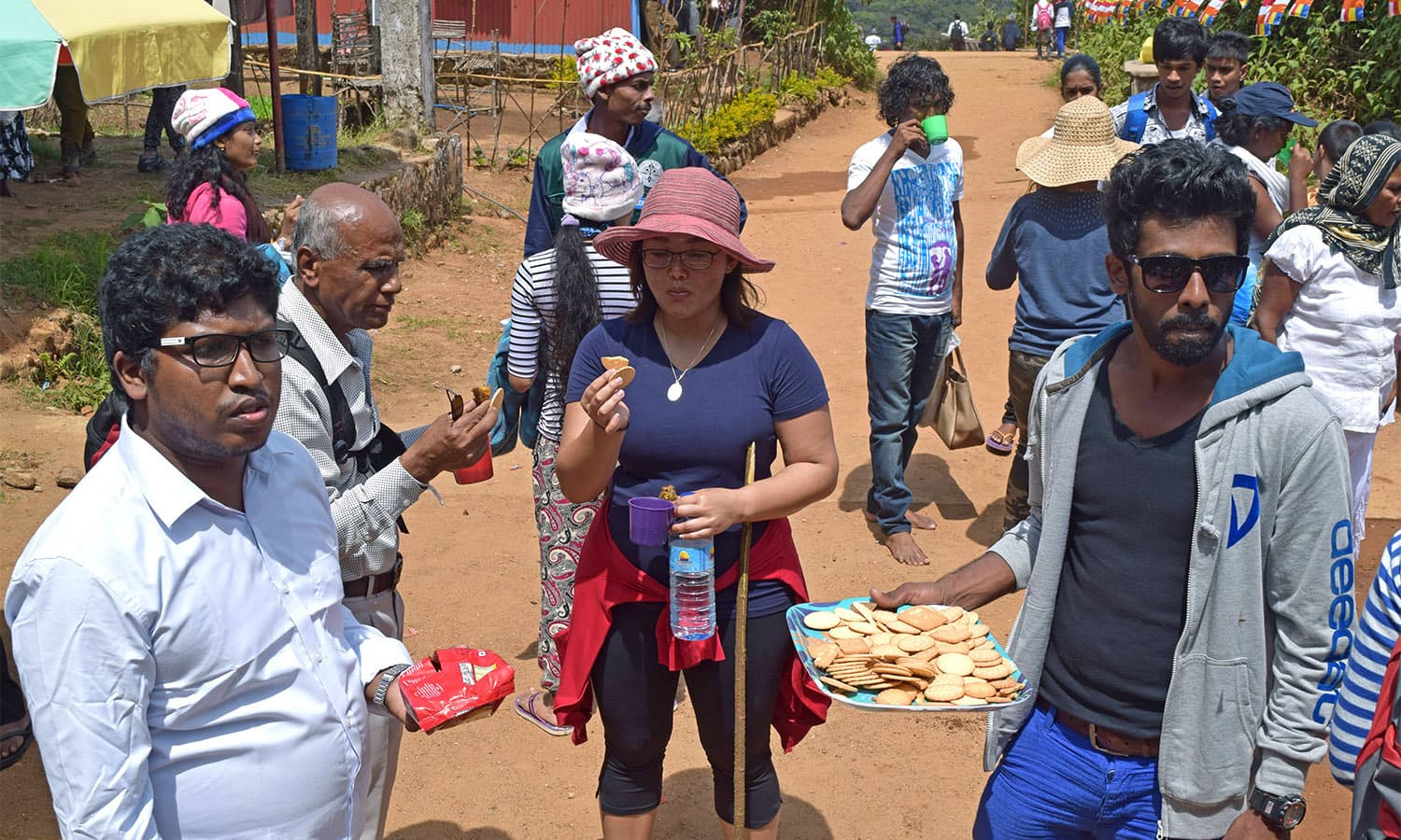 Volunteers help hand out food and water to pilgrims. —Photo by the author