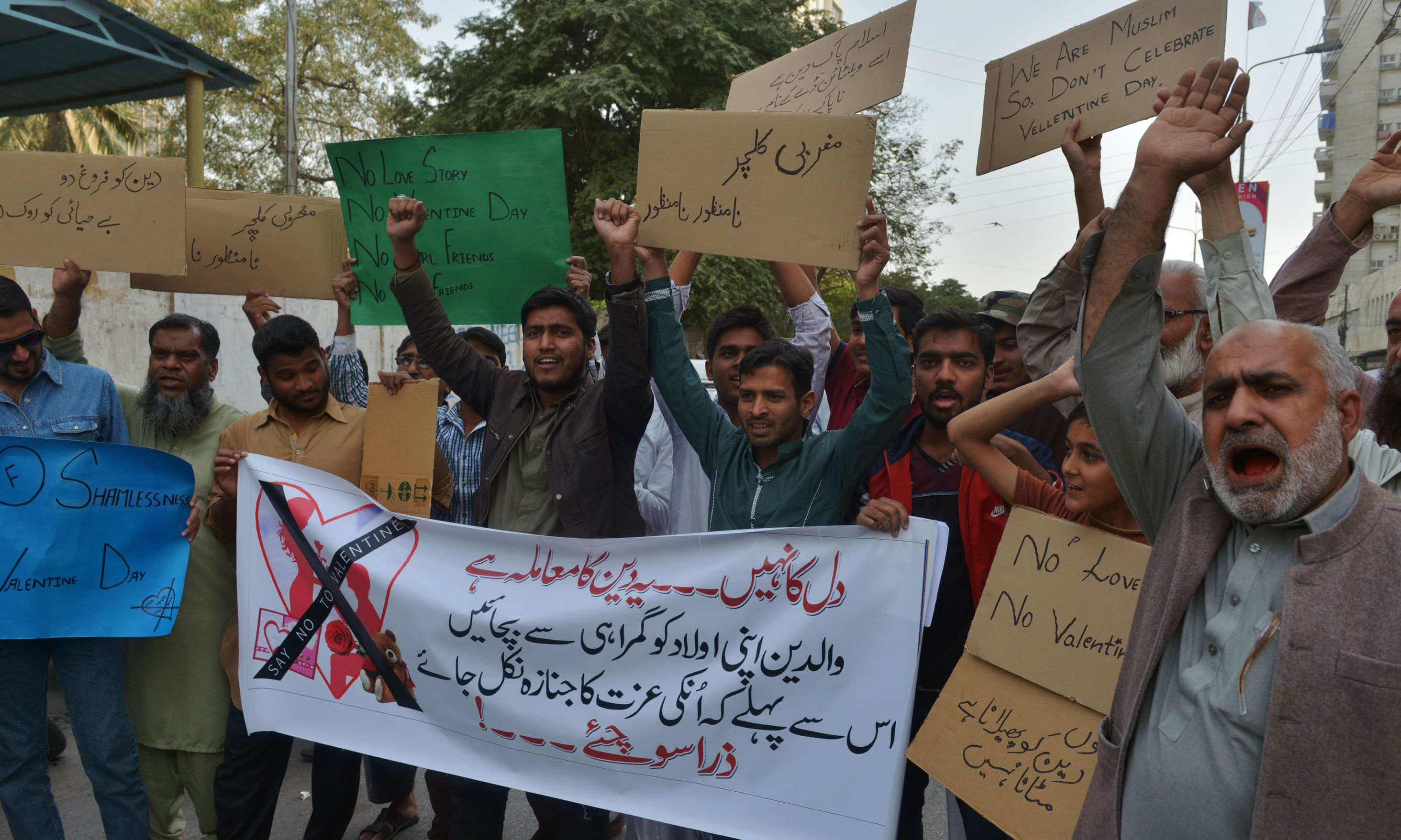 Demonstrators hold posters as they take part in a protest against Valentine's Day in Karachi. —AFP