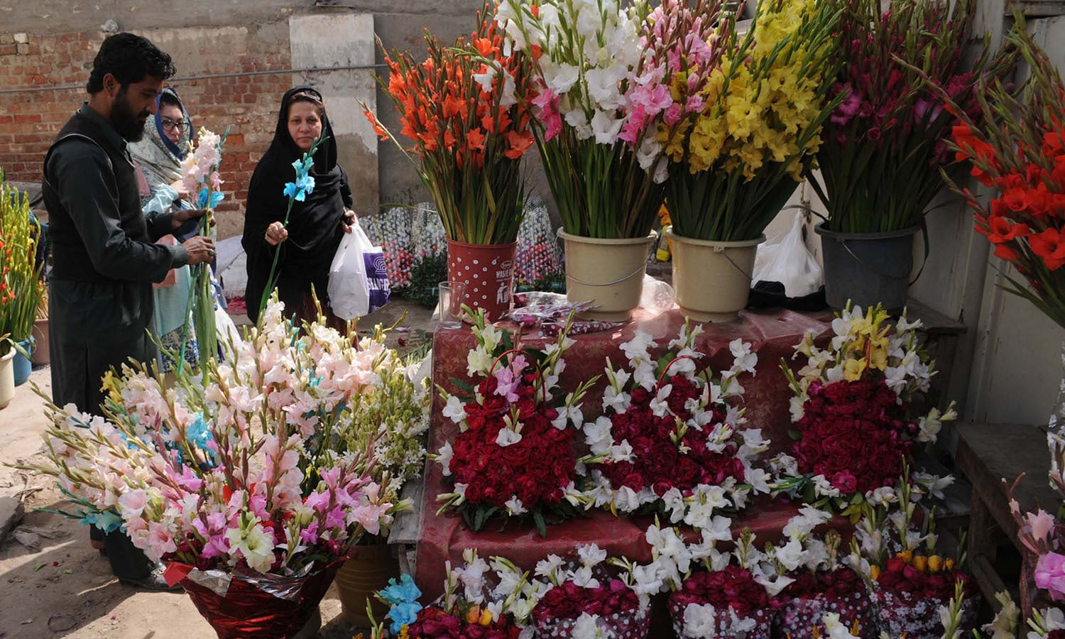 Women buying flowers for their loved ones on the occasion of  Valentine's Day, at a stall in Multan. ─PPI
