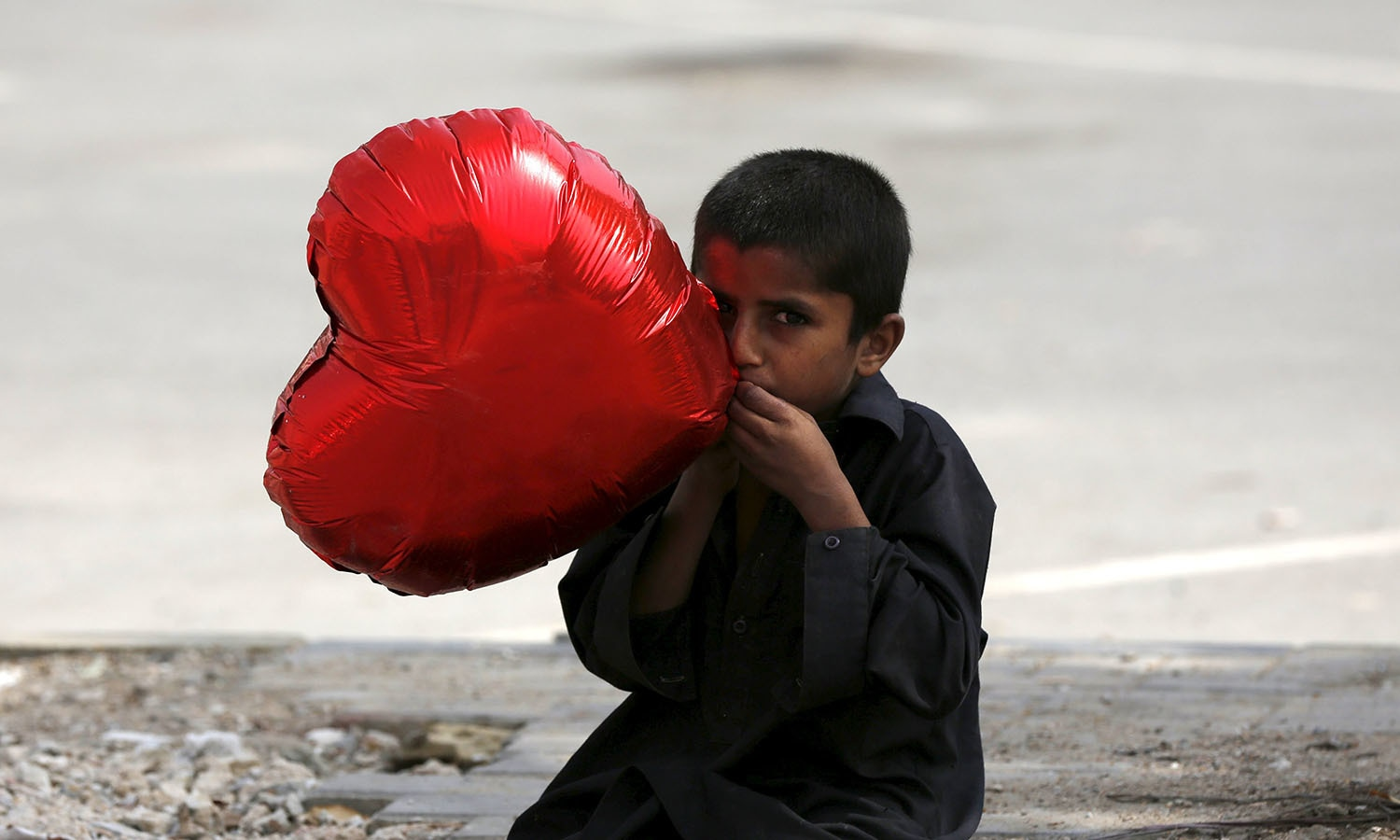 A boy inflates a heart-shaped balloon to sell on Valentine's Day in Karachi.─ Reuters