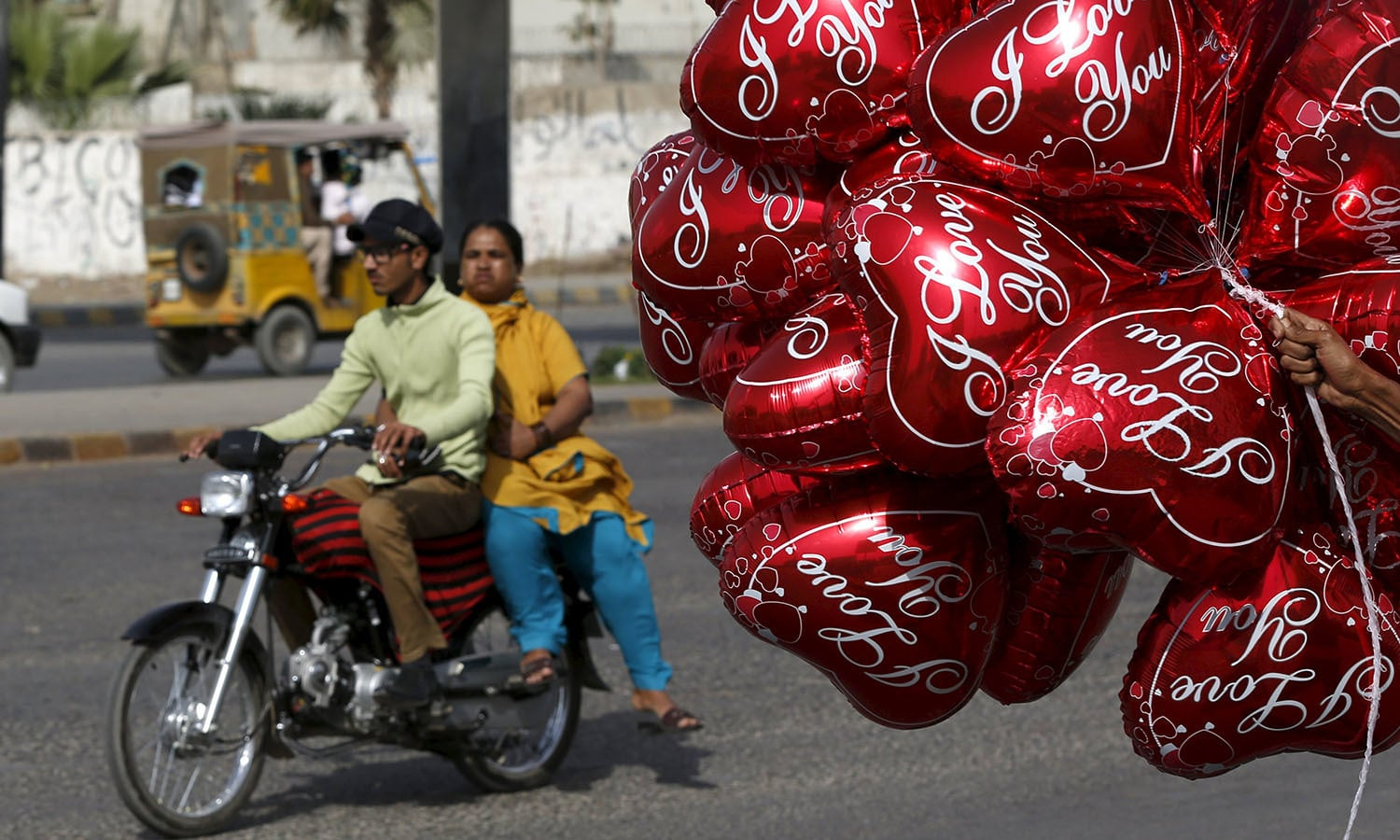 A couple on a motorcycle ride past a vendor selling heart-shaped balloons on Valentine's Day in Karachi.─Reuters