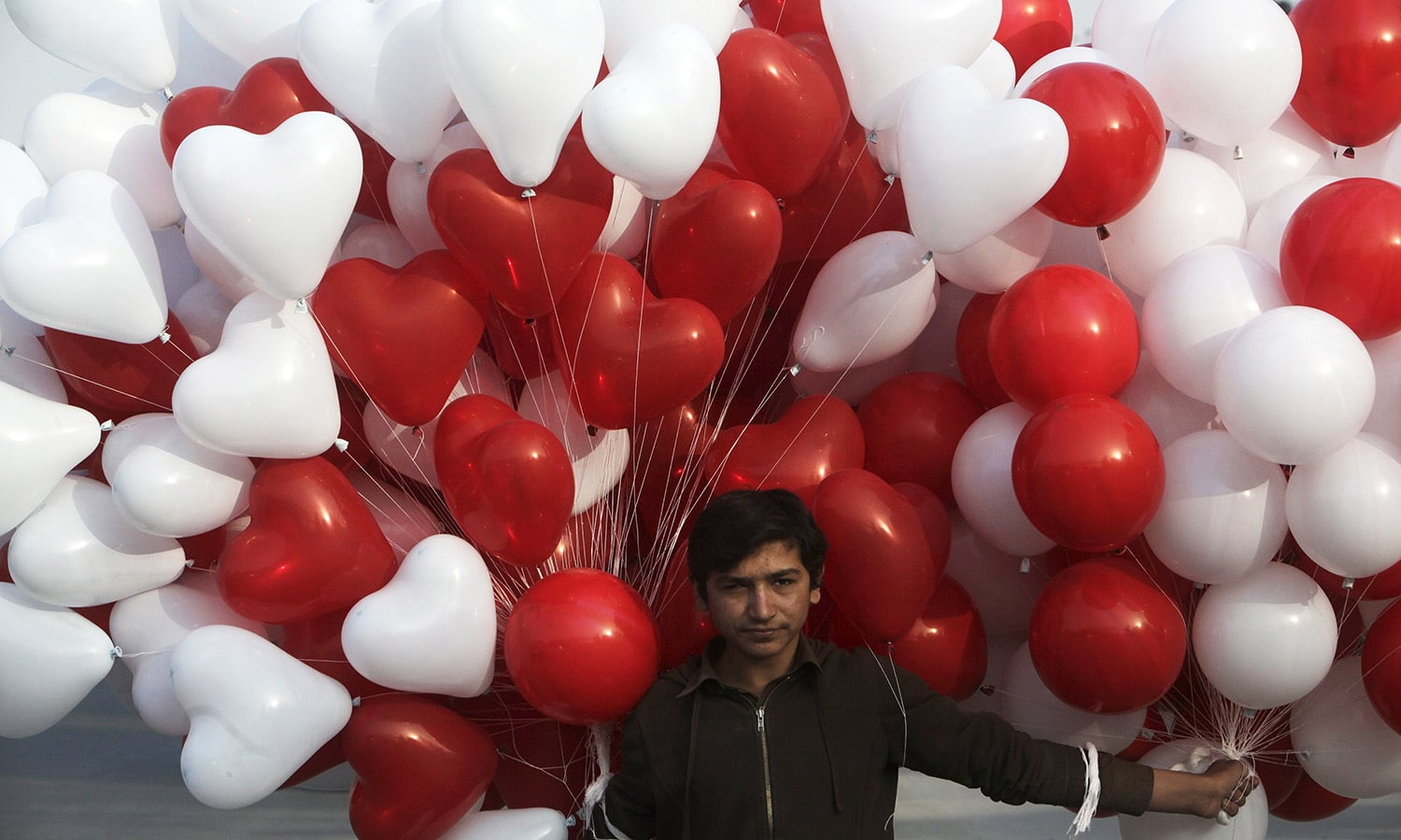 A vendor carries heart-shaped balloons for sale on Valentine's Day in Lahore.─Reuters