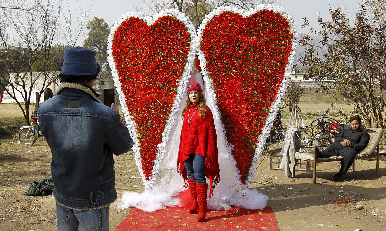 An Afghan man takes a picture of his sister in front of large heart shaped flower arrangement at a flower market on Valentine's Day in Islamabad.─Reuters