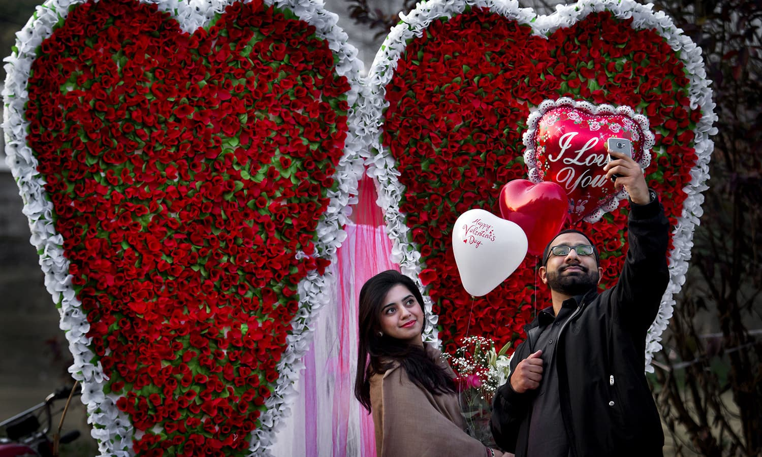 A couple take 'selfie' in front of a giant heart-shaped bouquet display by a vendor to attract customers on Valentine's Day, Sunday.─AP