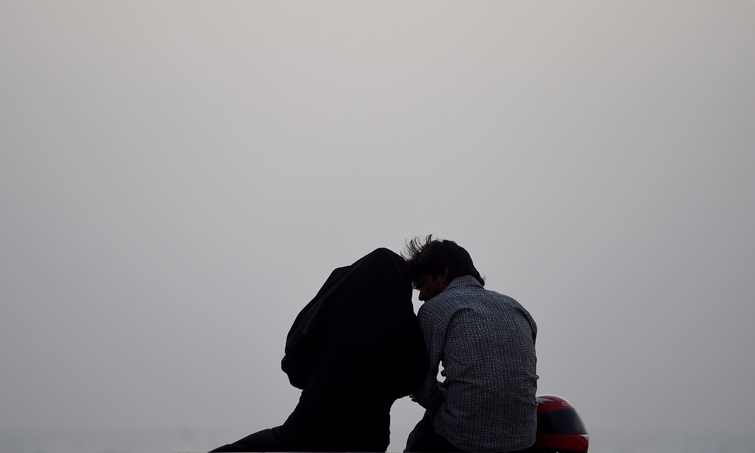 A Pakistani couple sits on a beach on Valentine's Day in Karachi.─AFP