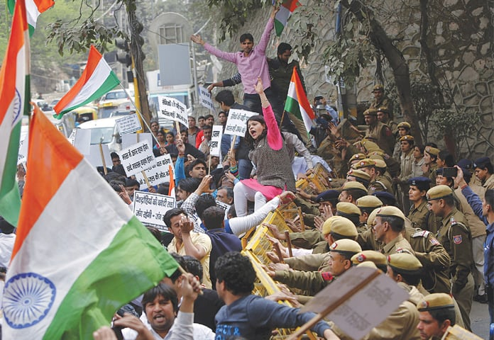 NEW DELHI: Police personnel stop demonstrators during a protest outside a university campus here on Monday.—Reuters