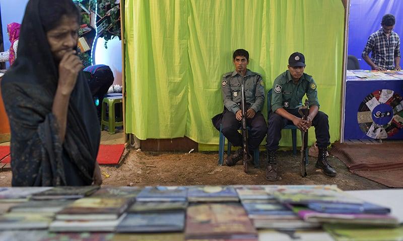 "Bangladeshi policemen guard outside a shutdown stall of ""Badwip Prokshan,"" a publishing house at a major month-long book fair in Dhaka. ─ AP"