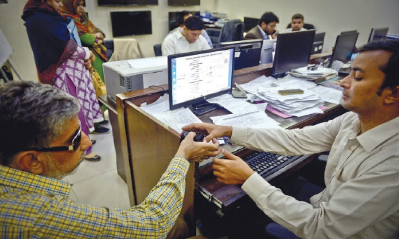 An associate professor at a girls college is being fingerprinted by the data cell staff head of biometric registration of teaching and non-teaching staff of schools and colleges in Sindh on Tuesday, the deadline given for the process.—Fahim Siddiqi/White Star