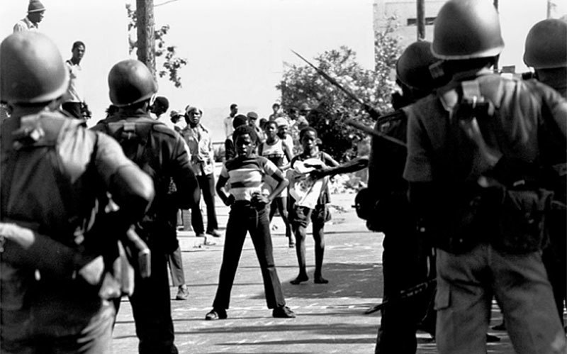 Streetkids face off against troops in Kingston, Jamaica (1976).