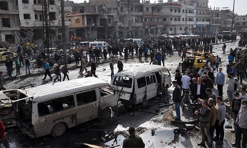 People gather at the site of a double car bomb attack in the Al-Zahraa neighbourhood of the central Syrian city of Homs.─AFP