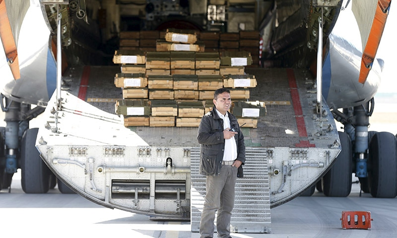 An Afghan security officer stands next to boxes of ammunition inside a Russian aircraft at the International Kabul Airport, Afghanistan.─Reuters