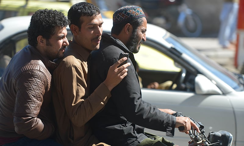 A Pakistani man sits on a motorbike as browses his phone on a street in Rawalpindi. ─ AFP