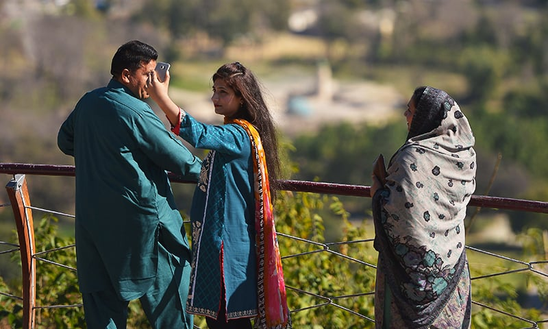 A young Pakistani woman takes a 'selfie' at a Margalla Hills viewpoint in Islamabad. ─ AFP