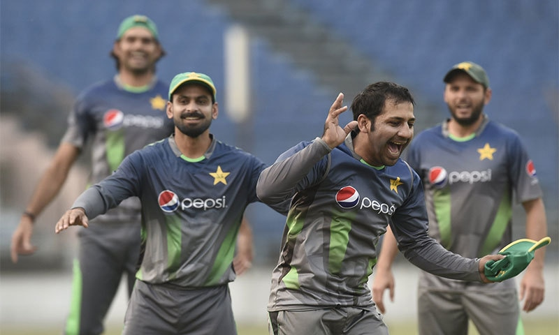 Sarfraz Ahmed plays football with teammates during a training session. — AFP