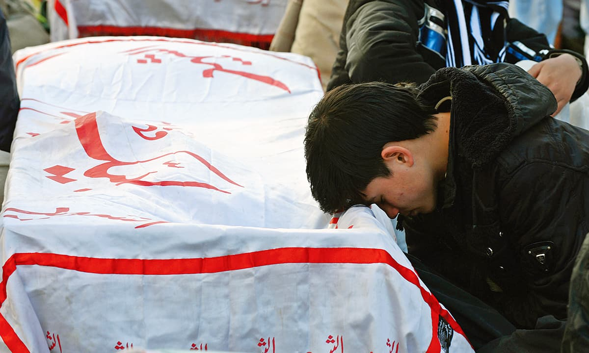 A young man mourns next to the coffin of his relative, killed in a deadly attack in Quetta on January 11, 2013 | AP