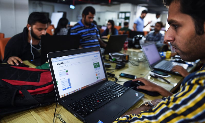 Employees of online marketplace company Kaymu at work in Karachi. ─ AFP