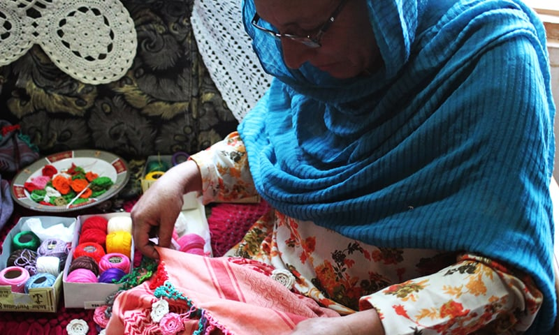 A Chitrali woman, who works with the artisan brand Kai, stitches a scarf. ─ AFP