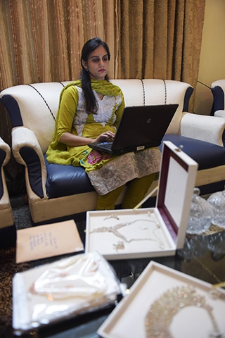 Nosheen Kashif, a vendor partnered with Kaymu working on a laptop at her residence in Islamabad. ─ AFP