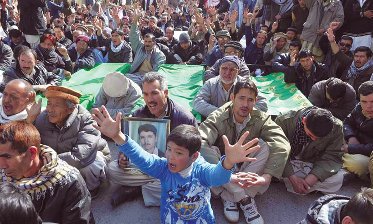Hazara mourners shout slogans as they gather next to the coffins carrying the remains of those killed in a blast in Quetta in 2013 | AFP