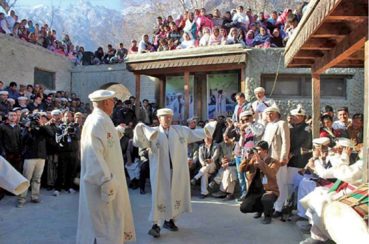 Local people and tourists watch a traditional dance at the festival on Sunday. — Dawn