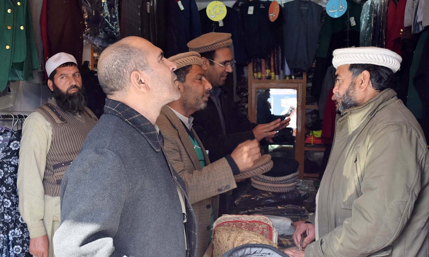 Men trying on Swati caps in Swat Cap House. ─ Photo by author