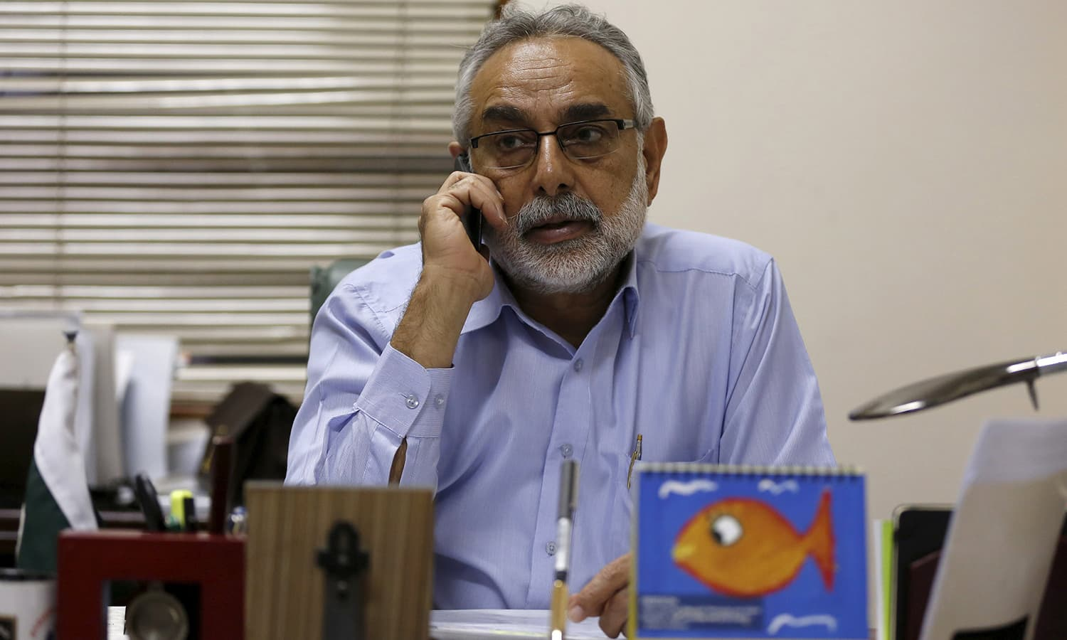 Zubair Habib, Chief of Citizen Police Liaison Committee (CPLC) talks on mobile phone at his office in Karachi, February 9, 2016. — Reuters