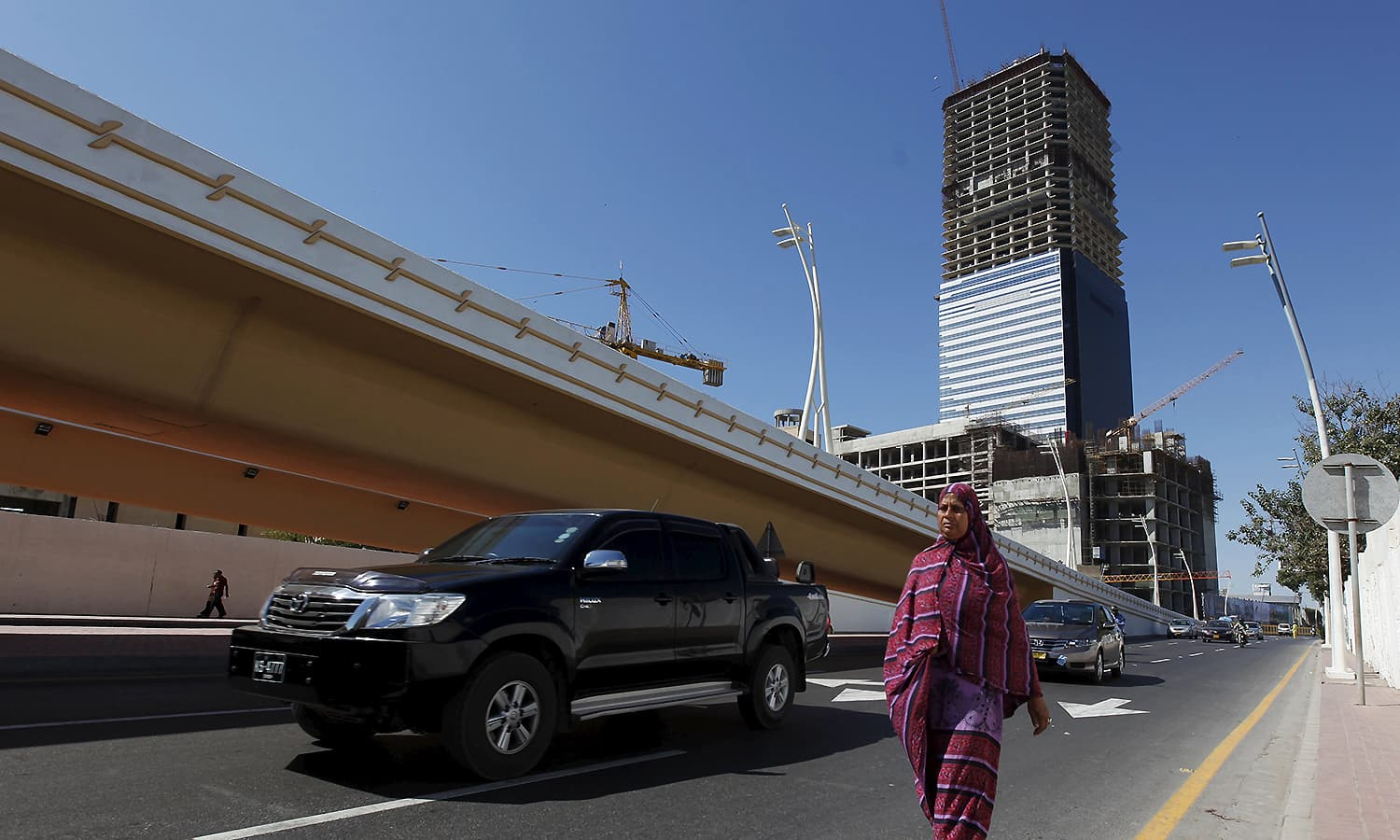 The construction site of the Bahria Icon 62 story building is seen in the background as a woman walks along a street in Karachi, February 9, 2016. — Reuters
