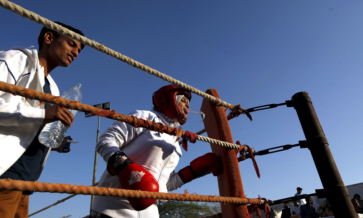 Urooj, 15, spits water between rounds in her bout during the Sindh Junior Sports Association Boxing Tournament. —Reuters