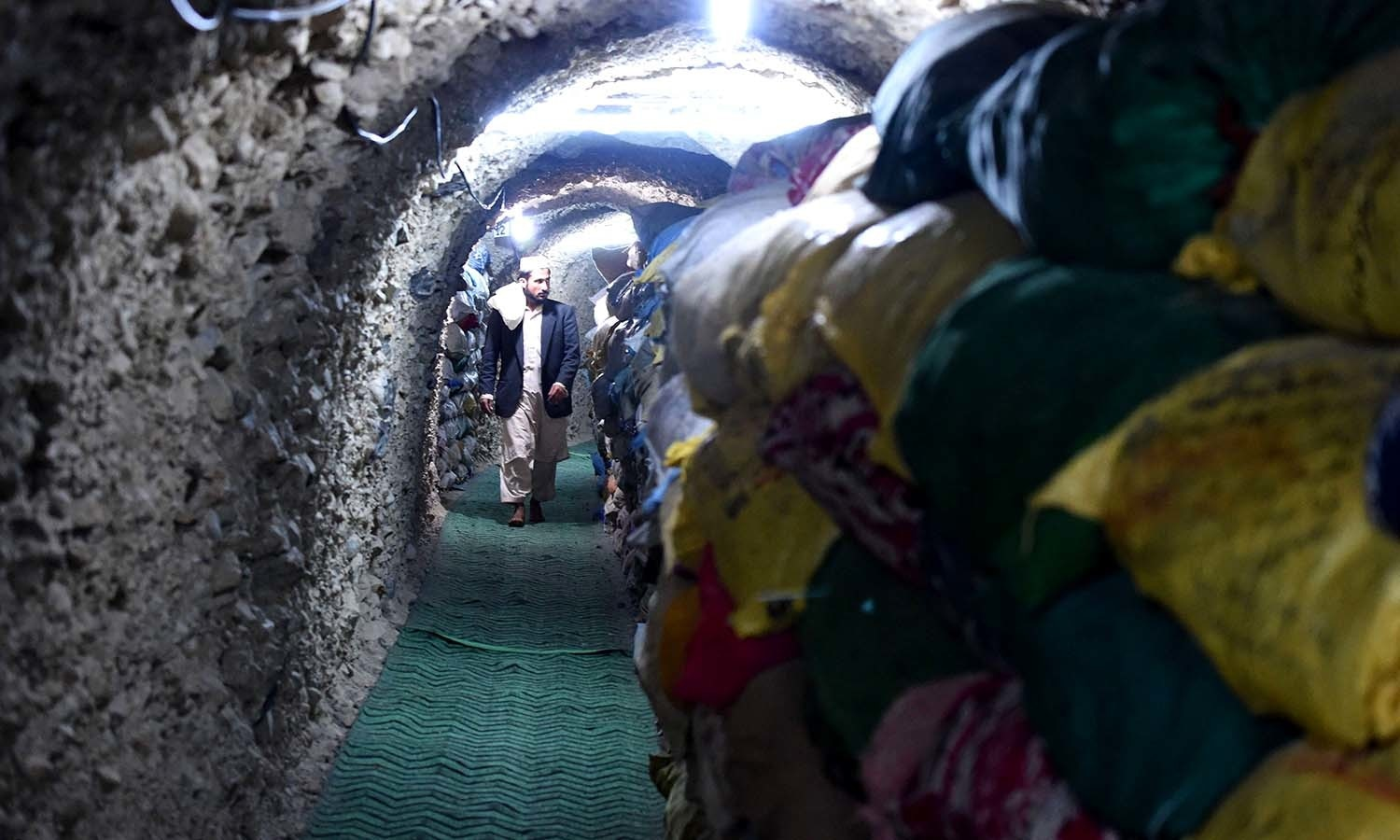 A devotee visiting a tunnel where ancient copies of the Quran are preserved. ─ AFP