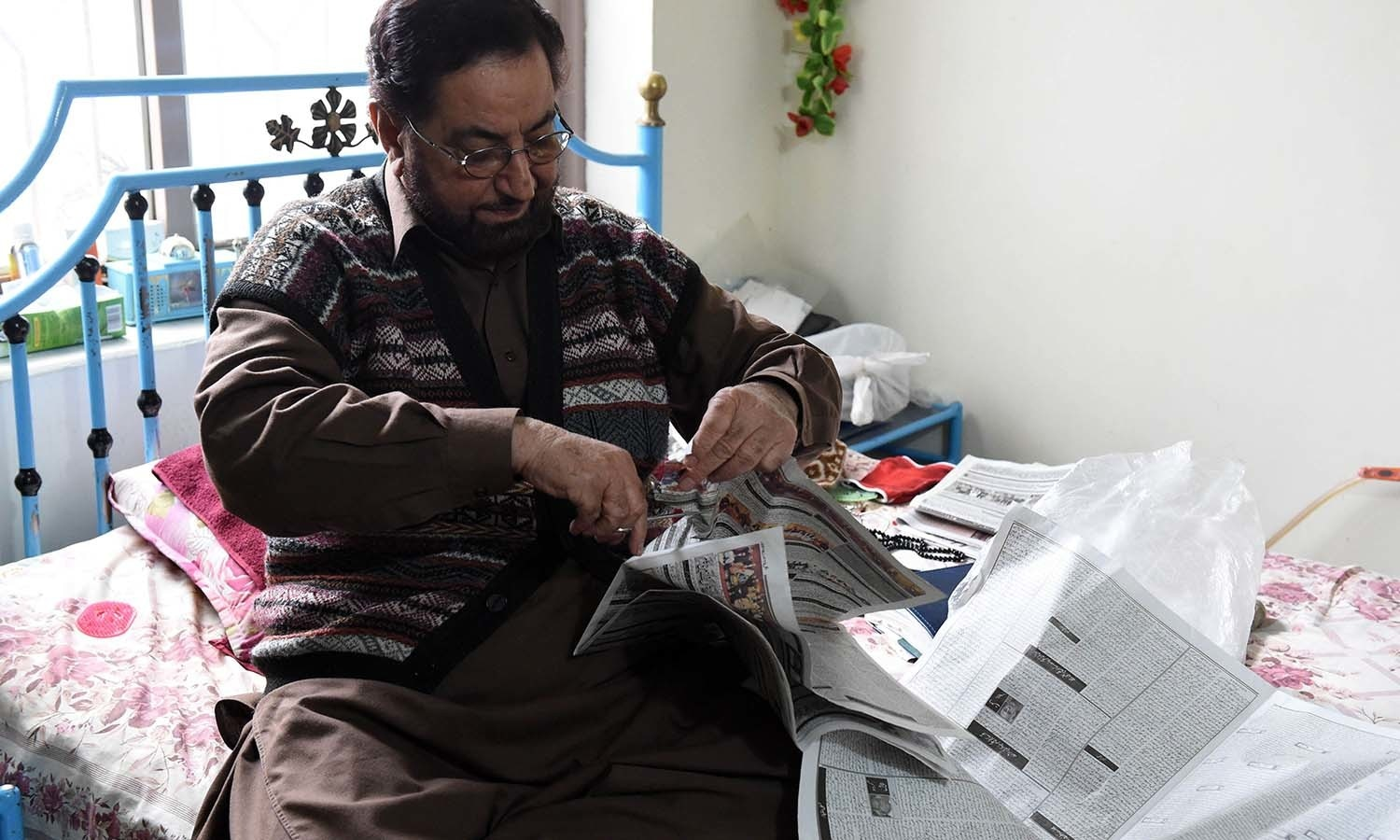 Haji Abdul Sammad Lehri cuts verses of the Quran from a newspaper at his residence. ─ AFP