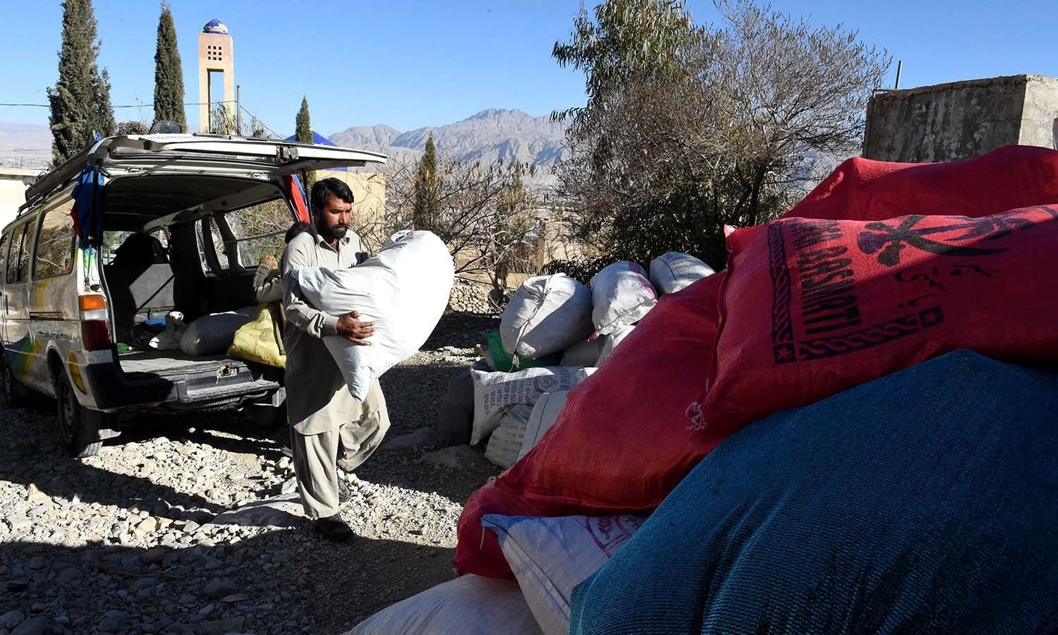 A volunteer unloading a sack containing old copies of the Quran from a van after collecting them from different places in Quetta. ─ AFP