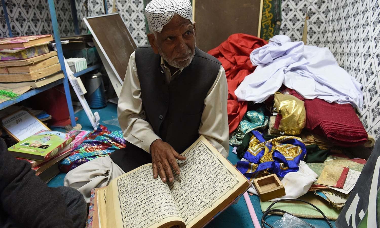 Haji Muzaffar Ali, the administrator of Jabl-e-Noor, examining an old copy of the Quran in a tunnel. ─ AFP