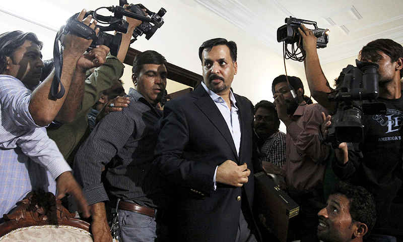 Former mayor Karachi Mustafa Kamal walks past cameramen before the news conference. ─Reuters