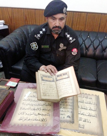 An excise official shows the seized books to media persons in Peshawar on Friday. —Dawn